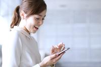 スマートフォンを見て笑うビジネス女性 33000003103| 写真素材・ストックフォト・画像・イラスト素材|アマナイメージズ