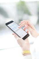 スマートフォンを操作するビジネス女性の手元