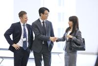 オフィスビルのロビーで握手をするビジネス女性