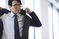 オフィスでスーツのジャケットを羽織るビジネス男性 33000003136| 写真素材・ストックフォト・画像・イラスト素材|アマナイメージズ