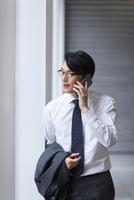 歩きながらスマートフォンで通話するビジネス男性