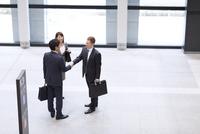 オフィスビルのエントランスで立って握手をするビジネス男女