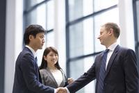 オフィスビルのエントランスで握手をするビジネス男性 33000003158| 写真素材・ストックフォト・画像・イラスト素材|アマナイメージズ