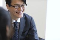 オフィスビルのロビーで笑うビジネス男性 33000003176| 写真素材・ストックフォト・画像・イラスト素材|アマナイメージズ