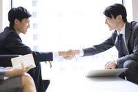 オフィスビルのロビーで握手をするビジネス男性