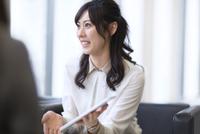 タブレットPCを持ち打ち合せをするビジネス女性 33000003198| 写真素材・ストックフォト・画像・イラスト素材|アマナイメージズ