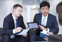 タブレットPCを持ち打ち合せをするビジネス男性