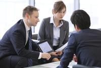 タブレットPCを持ち打ち合せをするビジネス男女 33000003212| 写真素材・ストックフォト・画像・イラスト素材|アマナイメージズ