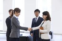 オフィスビルのロビーで握手をするビジネス男女