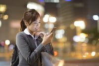 夜の街を背景にスマートフォンを見て微笑むビジネス女性