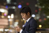 夜の街を背景にタブレットPCを見て微笑むビジネス男性 33000003236| 写真素材・ストックフォト・画像・イラスト素材|アマナイメージズ