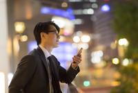 夜の街を背景にスマートフォンを持ち遠くを眺めるビジネス男性