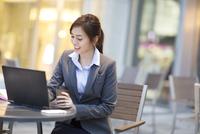 街中でノートPCを操作するビジネス女性