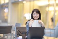 街中で手帳を持ち上を見上げ微笑むビジネス女性