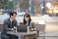 街中で会話しながらノートPCを操作する男女 33000003250| 写真素材・ストックフォト・画像・イラスト素材|アマナイメージズ