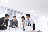 会議室で建築模型を使って打ち合せをするビジネス男女