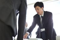 会議室で建築模型を使って打ち合せをするビジネス男性