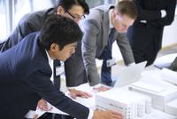 会議室で建築模型を使って打ち合せをするビジネス男性たち