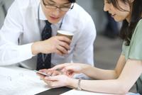 スマートフォンを使って打ち合せをするビジネス男女 33000003289| 写真素材・ストックフォト・画像・イラスト素材|アマナイメージズ