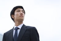 オフィスビルを背景に上を見上げるビジネス男性