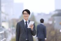 タブレットPCを持ち遠くを眺めるビジネス男性