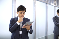 オフィスの廊下でタブレットPCを操作するビジネス男性