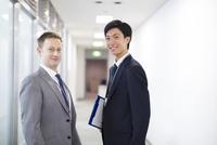 オフィスの廊下で微笑むビジネス男性2人
