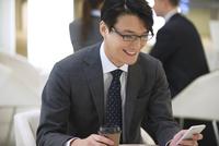 オフィスビルのロビーでスマートフォンを見て微笑むビジネス男性