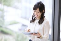 タブレットPCを見て微笑むビジネス女性