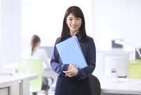 オフィスでファイルを持って微笑むビジネス女性