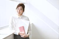 資料と手帳を持って微笑むビジネス女性