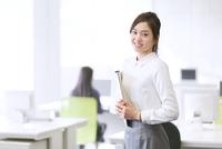 オフィスで資料を持って微笑むビジネス女性