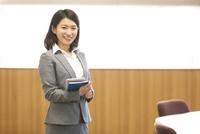 タブレットPCと手帳を持って微笑むビジネス女性