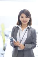 オフィスでタブレットPCと手帳を持って微笑むビジネス女性