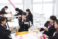 教室でお弁当を食べながら笑う学生たち