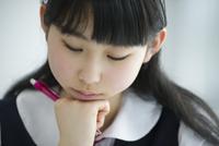 教室でペンを持ち考える女子学生