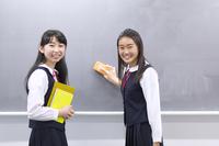 黒板の前で笑う女子学生2人