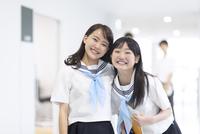 学校の廊下で笑う女子学生2人