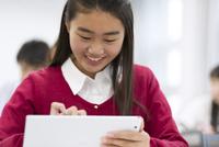 タブレットPCを持って授業を受ける女子生徒
