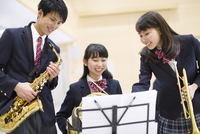 楽器を持って楽譜見る学生たち