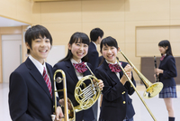 楽器を持って笑う男子学生と女子学生
