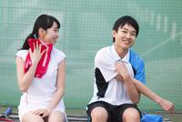 テニスコートでリラックスをする男子学生と女子学生