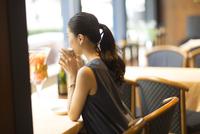 カフェでコーヒーを飲んでくつろぐ女性の後ろ姿