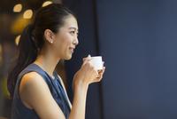 カフェでカップを持ってくつろぐ女性の横顔