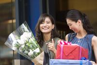 花束やプレゼントボックスを持って店を出る女性2人 33000003805| 写真素材・ストックフォト・画像・イラスト素材|アマナイメージズ