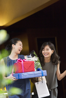 花束やプレゼントボックスを持って店を出る女性2人