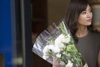 花束を持って遠くを見る女性