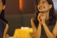 レストランで手を組んで笑う女性