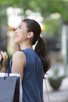 街角で上を見上げ微笑む女性