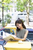 オープンカフェで新聞を読む女性